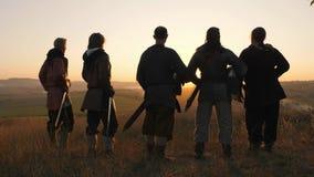 Los guerreros vikingos se colocan en campo y miran puesta del sol hermosa en el campo de batalla almacen de video
