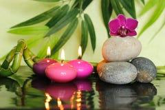 Los guijarros arreglaron en forma de vida del zen en la derecha con una orquídea en el top y las velas rosadas encendidos Fotos de archivo