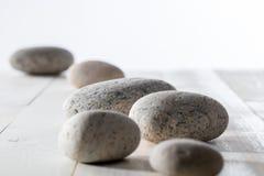 Los guijarros fijaron en el fondo de madera blanco para el mindfulness o la yoga Imagenes de archivo