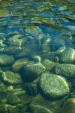Los guijarros lisos grandes ondulan debajo del agua de restauración en el río imagen de archivo libre de regalías