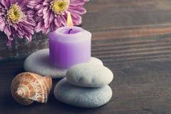 Los guijarros, púrpura encendieron la vela, flores, cáscaras Fotografía de archivo
