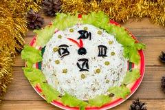 Los guisantes de verdes de aceitunas del arroz de la ensalada de la Navidad - cara de reloj del Año Nuevo del concepto, medianoch Imágenes de archivo libres de regalías