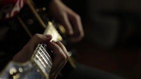 Los guitarristas de una banda de rock juegan en la guitarra, las manos del primer y cuello de la guitarra metrajes