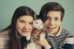 Los hermanos adolescentes muchacho y muchacha abrazan con el gato Imagenes de archivo