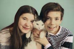 Los hermanos adolescentes muchacho y muchacha abrazan con el gato Foto de archivo