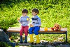 Los hermanos de niños que se sientan en banco de madera juegan con el caucho du Imagenes de archivo