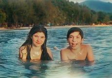 Los hermanos del adolescente juntan la natación del hermano y de la hermana en el mar Imagen de archivo
