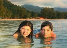 Los hermanos del adolescente juntan la natación del hermano y de la hermana en el mar Fotografía de archivo