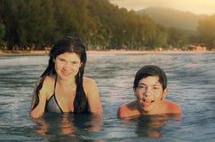 Los hermanos del adolescente juntan la natación del hermano y de la hermana en el mar Fotos de archivo libres de regalías