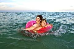 Los hermanos en un anillo de la nadada se divierten en el océano Imagen de archivo