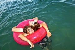 Los hermanos en un anillo de la nadada se divierten en el océano Imagenes de archivo
