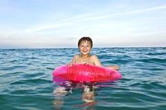 Los hermanos en un anillo de la nadada se divierten en el océano Fotos de archivo libres de regalías