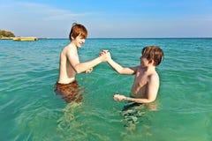 Los hermanos están gozando del agua caliente clara en el beac hermoso Fotografía de archivo