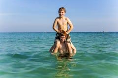 Los hermanos están gozando del agua caliente clara en el océano y el juego Fotos de archivo