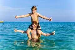 Los hermanos están gozando del agua caliente clara en el océano y el juego foto de archivo libre de regalías