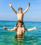 Los hermanos están gozando del agua caliente clara en el océano y el juego Fotografía de archivo libre de regalías