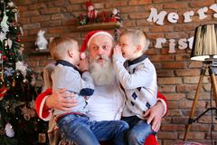 Los hermanos felices de los muchachos susurran simultáneamente en el oído de la Navidad Foto de archivo