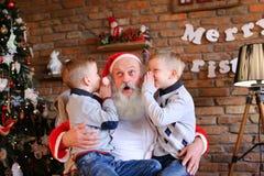 Los hermanos felices de los muchachos susurran simultáneamente en el oído de la Navidad Imagen de archivo