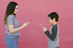 Los hermanos hablan el uno al otro usando sus teléfonos que mandan un SMS a la comunicación de los tiempos modernos del concepto imagen de archivo