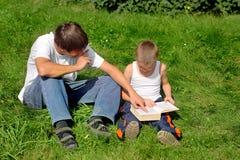 Los hermanos leen el libro Foto de archivo libre de regalías