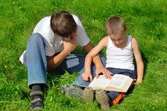 Los hermanos leen el libro Imagen de archivo