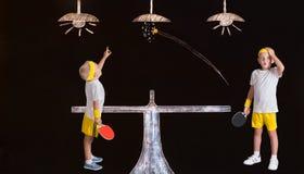 Los hermanos que jugaban a tenis de mesa y rompieron accidentalmente la lámpara Dibujos en tiza en la pared imagenes de archivo