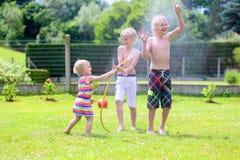 Los hermanos y la hermana que juegan con agua riegan en el jardín Fotografía de archivo