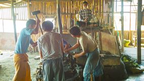 Los herreros están trabajando juntos en la producción de armas en la herrería Foto de archivo