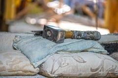 Los herreros pesados martillan con la manija envuelta en trapos ponen en las almohadas viejas y el paño en los herreros pasados d imagen de archivo libre de regalías