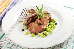 Los hígados de pollo frito con los guisantes y el romero de nieve en un blanco plat Fotografía de archivo