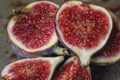 Los higos maduros rojos dulces en un manojo de mentiras en un metal hermoso se colocan Imagen de archivo libre de regalías