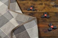 Los hilanderos hechos a mano de madera raros mienten en una tela escocesa a cuadros en una superficie de madera marrón del fondo  Fotos de archivo