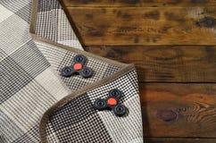 Los hilanderos hechos a mano de madera raros mienten en una tela escocesa a cuadros en una superficie de madera marrón del fondo  Imagen de archivo libre de regalías