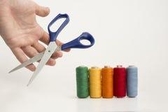 Los hilos del multicolor y una mano con Scissor fotos de archivo libres de regalías