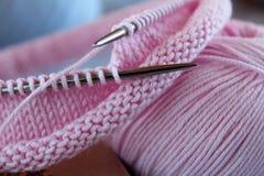 Los hilos que hacen punto rosados, las agujas que hacen punto y los lazos del punto mienten en la tabla Textura que hace punto fotografía de archivo
