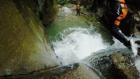 Los hombres activos saltan en la cascada mientras que selva tropical del ecuatoriano de la introducción del descenso de cañones almacen de metraje de vídeo