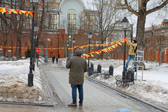 Los hombres adornan con las banderas coloridas en la ermita del parque para el día de fiesta en Moscú Imagenes de archivo