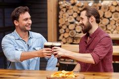 Los hombres amistosos alegres están hablando en pub Imagen de archivo libre de regalías