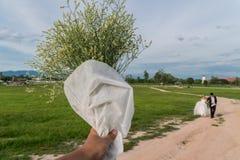 Los hombres asiáticos dan sostener las flores blancas a los pares de la boda Foto de archivo