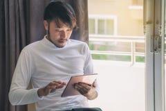 Los hombres asiáticos en las camisetas blancas están utilizando la tableta para trabajar en vaca imagenes de archivo