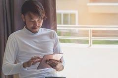 Los hombres asiáticos en las camisetas blancas están utilizando la tableta para trabajar en vaca fotografía de archivo