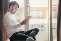 Los hombres asiáticos en las camisetas blancas están utilizando la tableta para trabajar en vaca imágenes de archivo libres de regalías