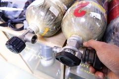 Los hombres asiáticos están comprobando los tanques de oxígeno imagen de archivo