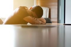 Los hombres asiáticos son el caer dormido en el escritorio imágenes de archivo libres de regalías