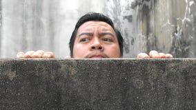 Los hombres asiáticos suben para arriba los muros de cemento imagenes de archivo