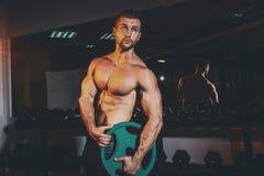 Los hombres atléticos fuertes musculares que bombean para arriba muscles y que entrenan en gimnasio Individuo hermoso del culturi Imagen de archivo libre de regalías