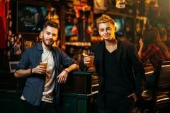 Los hombres aumentaron sus vidrios con la cerveza en un pub del deporte Imagenes de archivo