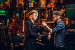 Los hombres aumentaron sus vidrios con la cerveza en un pub del deporte Imágenes de archivo libres de regalías