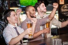 Los hombres avivan agitar sus manos y la observación de fútbol en la TV y el drin Imagen de archivo
