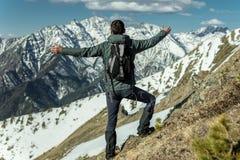 Los hombres celebran éxito separándose los brazos que se colocan en el fondo de montañas nevosas Logro de sus metas fotos de archivo libres de regalías